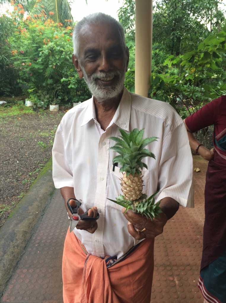 This is our dear friend Nair holding an ornamental pineapple plant. We have this in the car and need to plant it somewhere.
